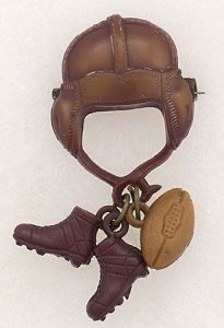 Bakelite tends to be dark colors, such as with this dark brown football pin.