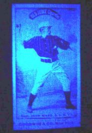 A modern 1880s Old Judge reprint fluorescing bright light blue under black light