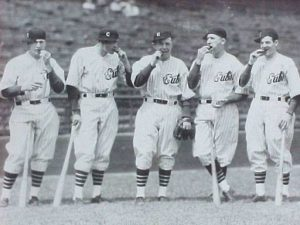 Chicago Cubs Teammates chewing tobacco, 1930s: (l-r) Billy Herman, Guy Bush, Bob Smith, Zach Taylor, Woody English.  The photo was shot by famous team photographer George Burke and printed later by his business partner George Brace.