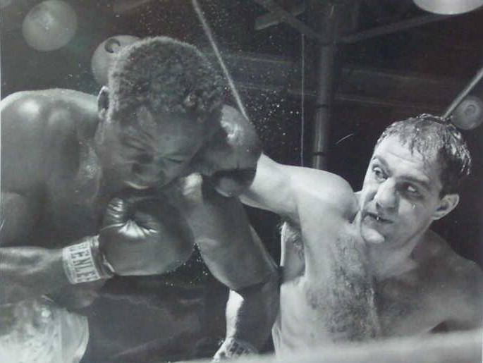 1954 news photo of Rocky Marciano versus Ezzard Charles heavyweight champion shot.  The photo was shot by famed Sports Illustrated photographer Herb Scharffman and has his name on back.