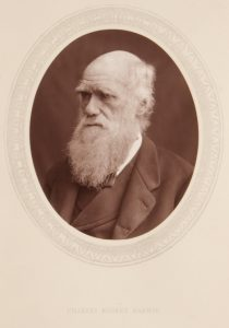 Book page with an oval woodburytype picture of Charles Darwin pasted in.