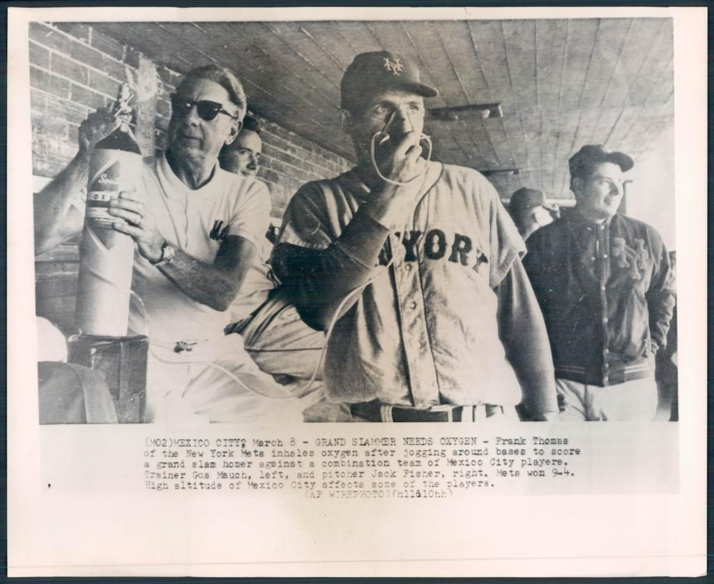 Frank Thomas taking oxygen in the dugout after hitting a grand slam. 1961 wirephoto with caption in the image and irregular border.