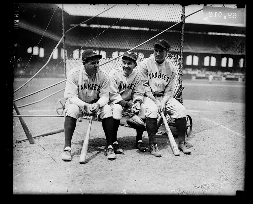 Group portrait of baseball players (left to right) Babe Ruth, Bob Shawkey, and Lou Gehrig of the American League's New York Yankees, sitting on a batting practice backstop on the field at Comiskey Park, Chicago, Illinois, 1930.  -Chicago History Museum photo.